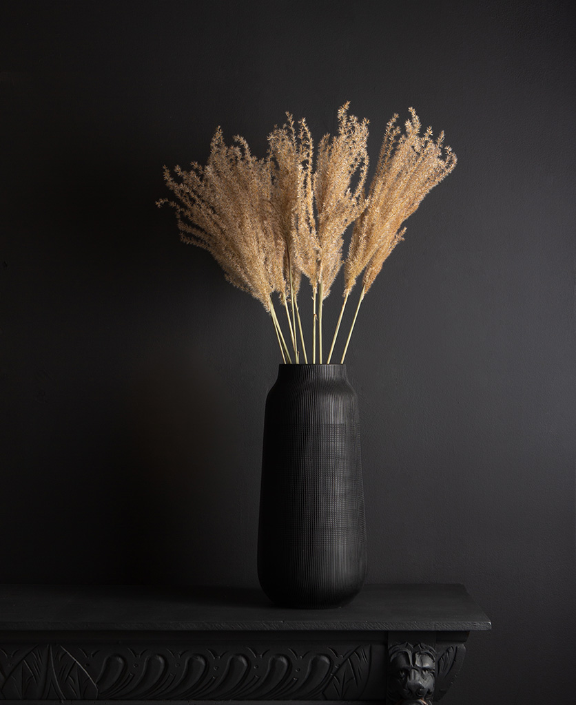 black tall vase with dried fluffy reed grass bouquet against black background