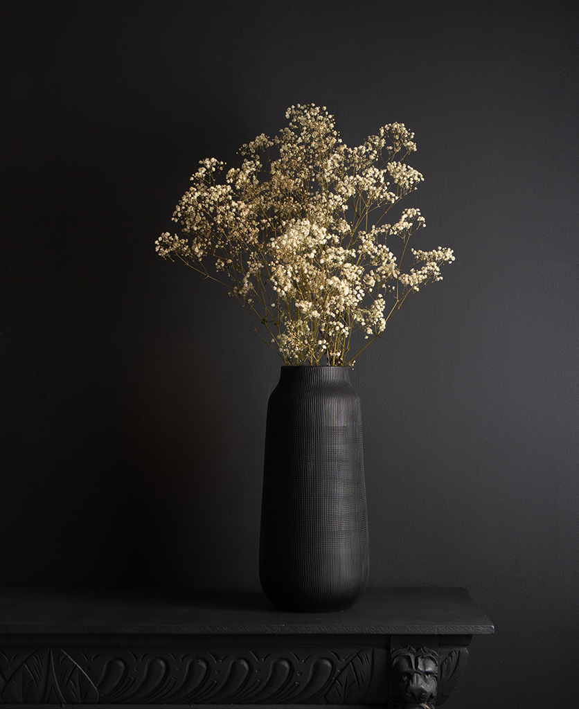 black tall vase with preserved gypsophila bouquet against black background