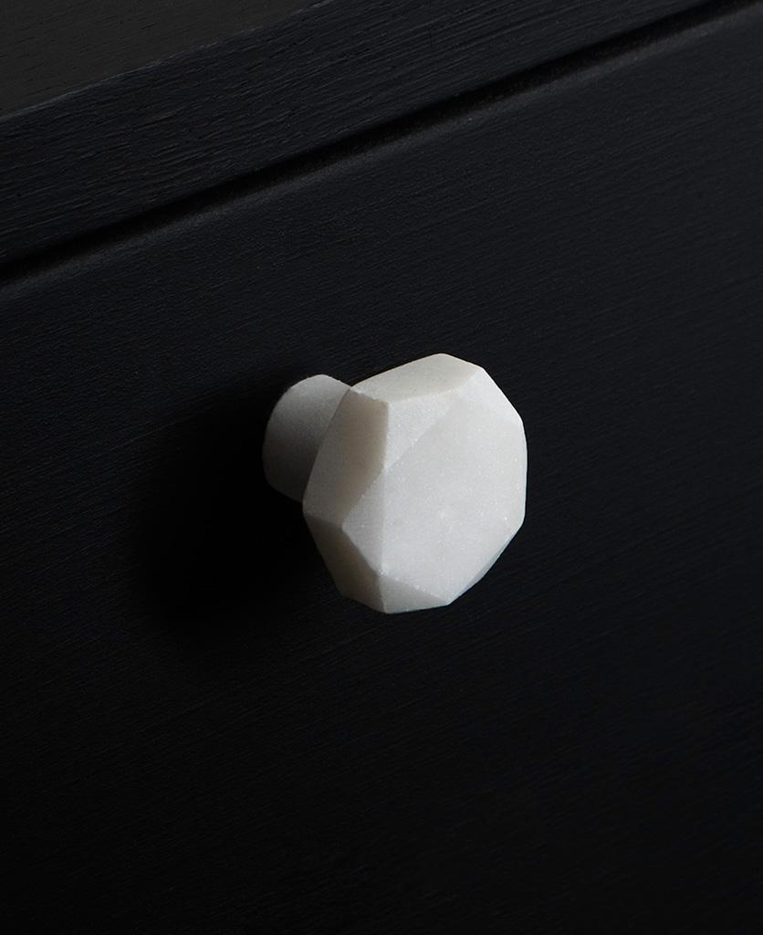 white faceted hexagonal marble door knobs on black drawer