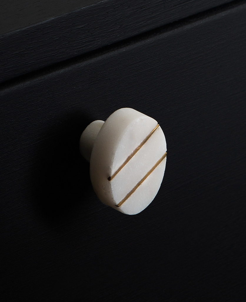 Barruzi white oval marble knob with two gold stripes on black drawer