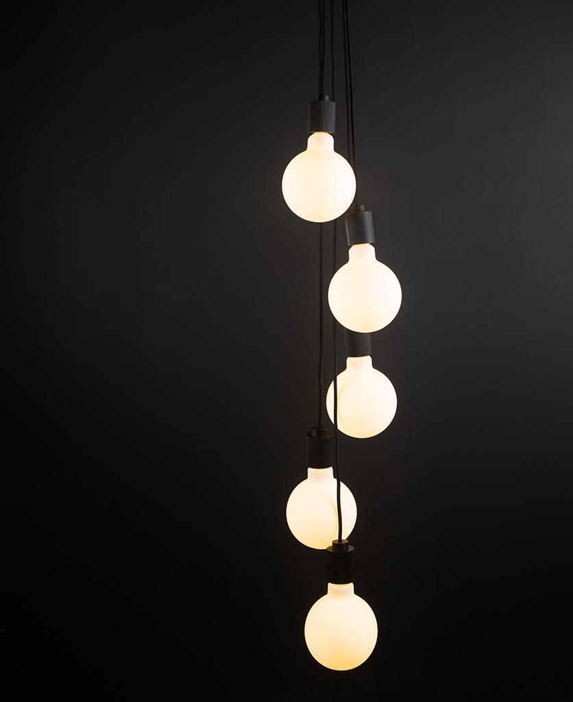 black spiral pendant light fitting with five bulbs on black background