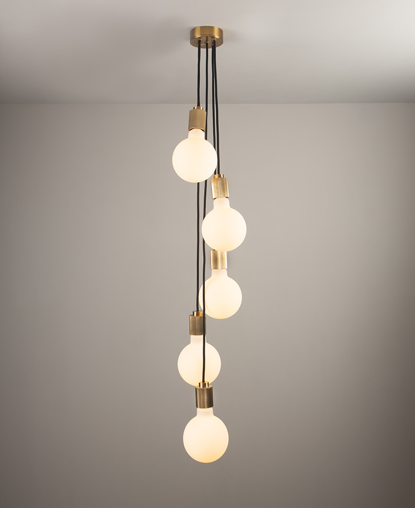 gold spiral pendant light fitting on grey background