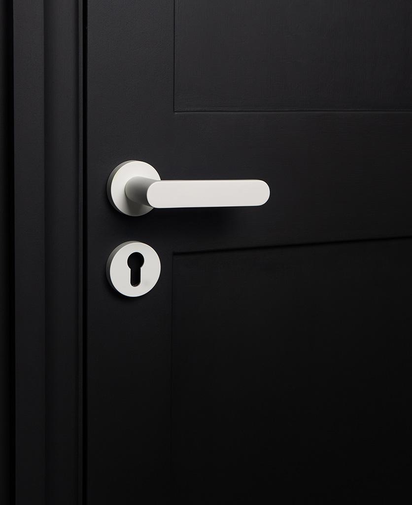 white internal door handle with escutcheon on black door