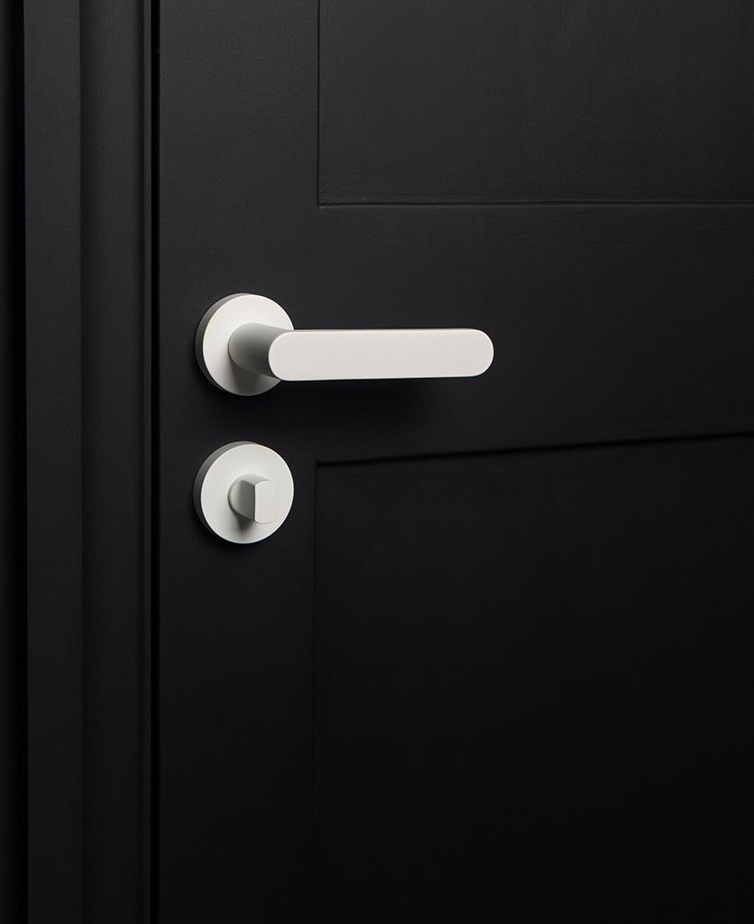 white internal door handle with thumb lock on black door