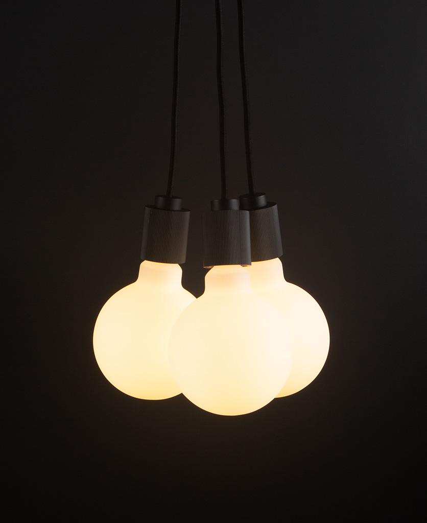 lutetia black triple pendant lighting with opal bulbs on black background