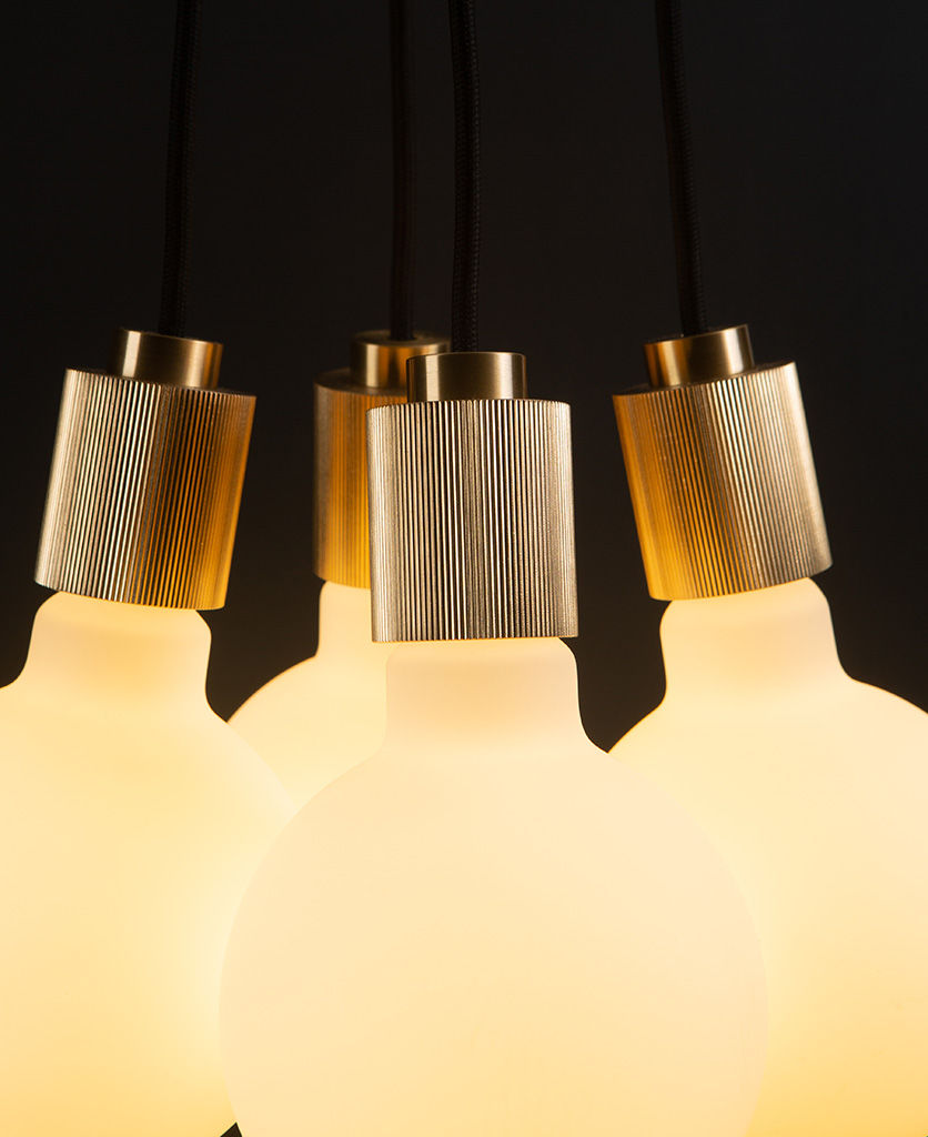 henriette gold pendant light close up with four opal bulbs on black background