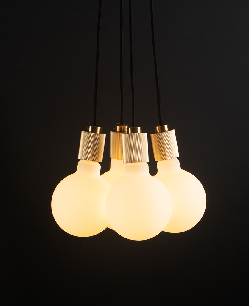 henriette gold pendant light with four opal bulbs on black background