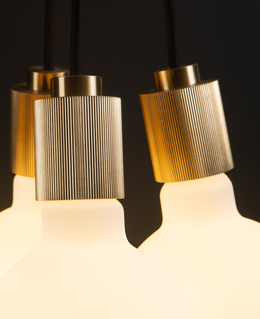 close up of lutetia gold pendant lighting on black background