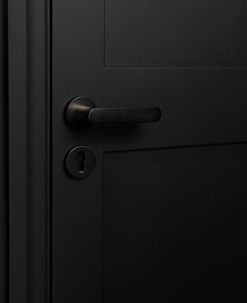 graphite interior door handles with escutcheon plate on black door