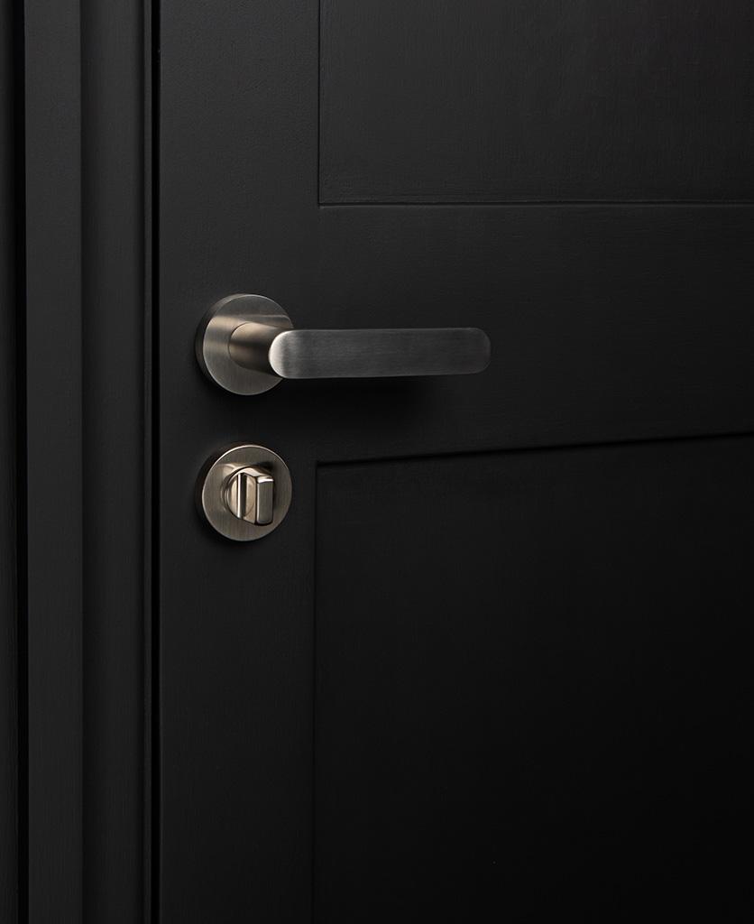 silver interior door handle with thumb lock on black door