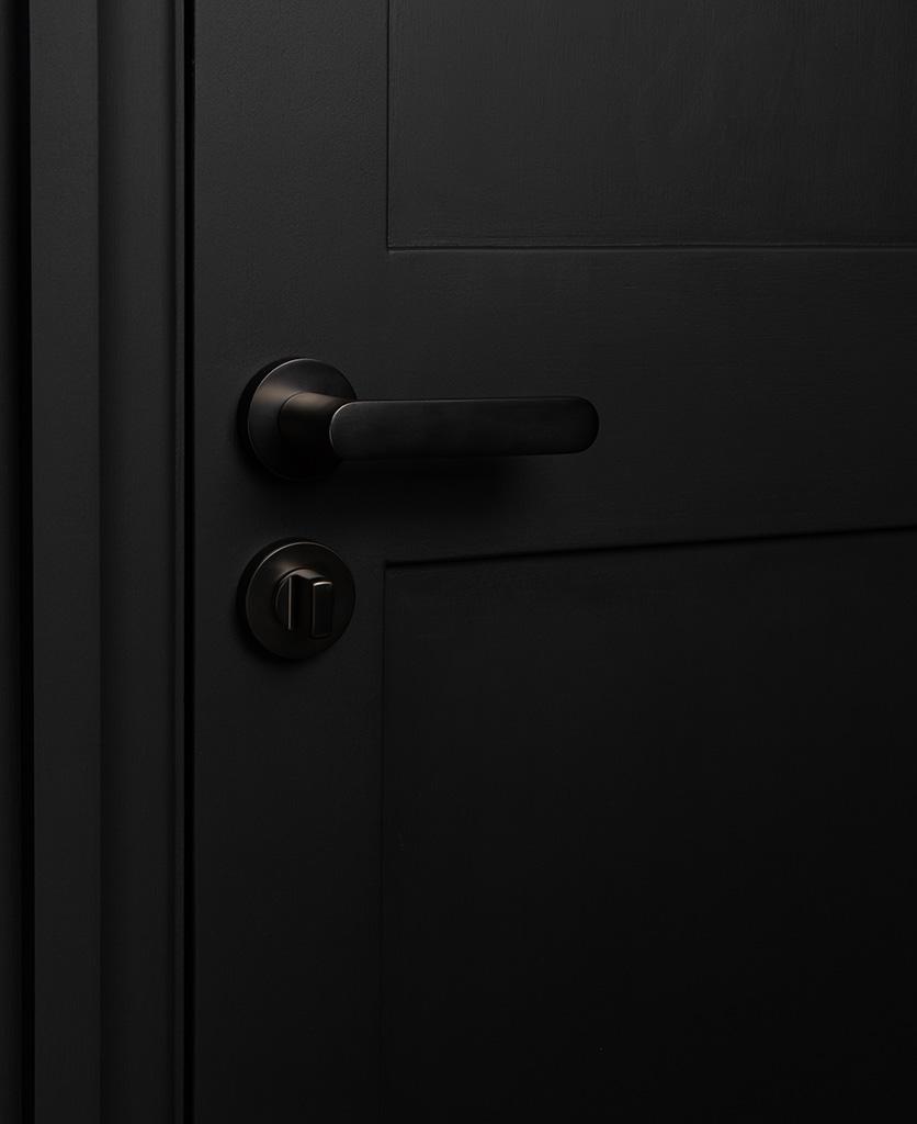 graphite interior door handle with thumb lock on black door