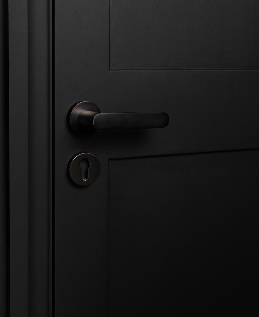 graphite interior door handle with escutcheon on black door