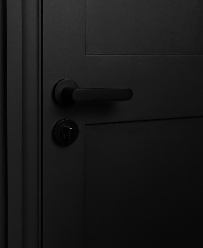 black interior door handle with thumb lock on black door
