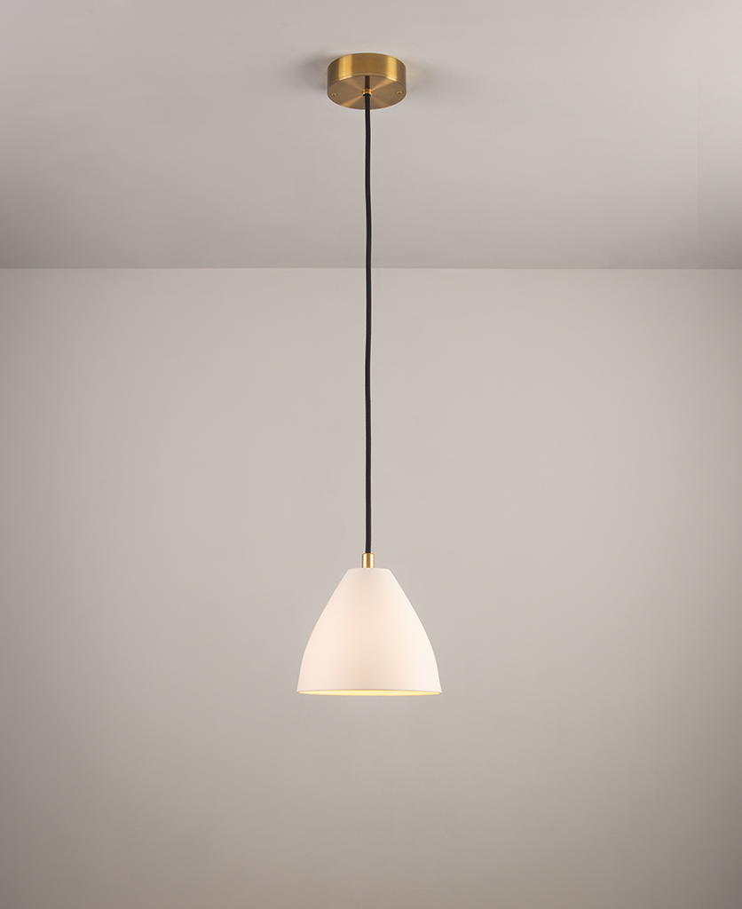white porcelain pendant light with gold detail and black fabric cable suspended against white background