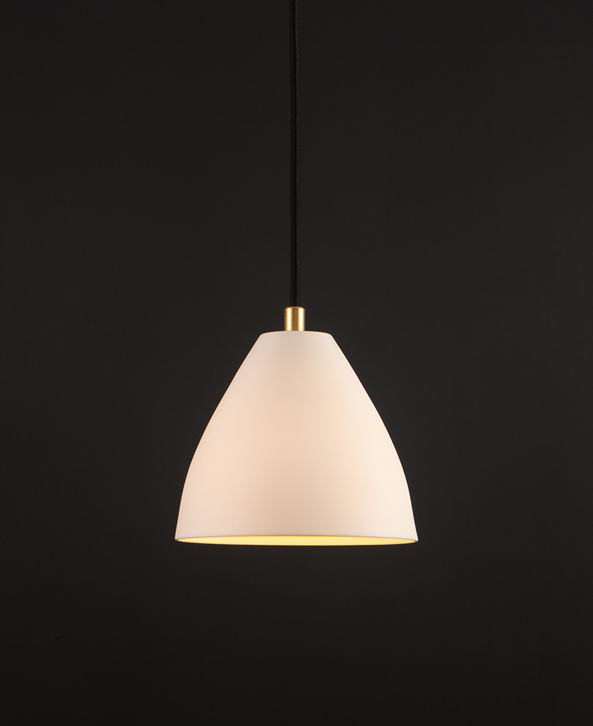 white porcelain pendant light with gold detail and black fabric cable suspended against black background