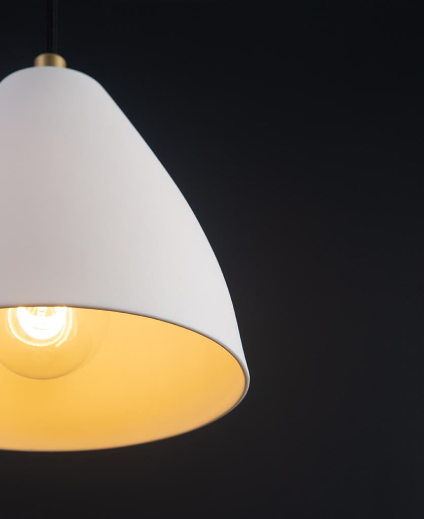 closeup of bulb in white and gold porcelain pendant light against black background