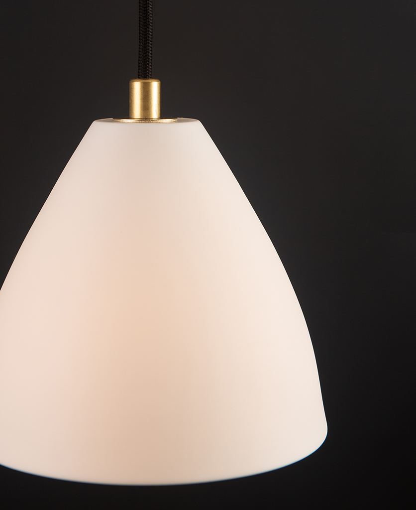 closeup of white and gold porcelain pendant light against black background