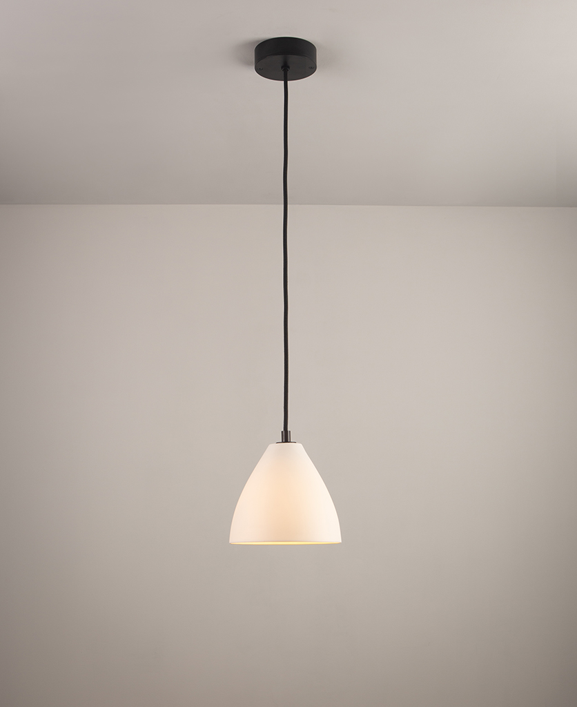 white porcelain pendant light with black detail and black fabric cable suspended against white background
