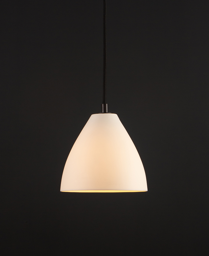 white porcelain pendant light with black detail and black fabric cable suspended against black background