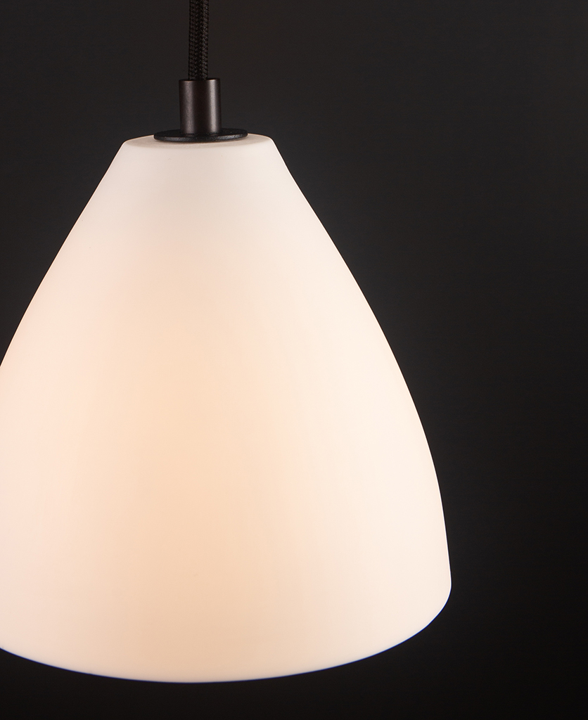 closeup of white and black porcelain pendant light against black background