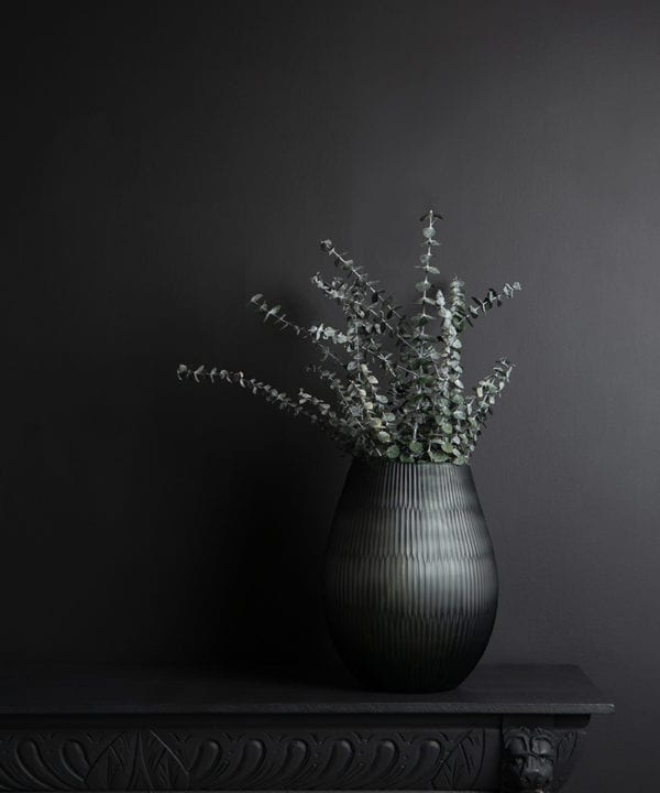Baby blue eucalyptus with grey textured vase on dark background