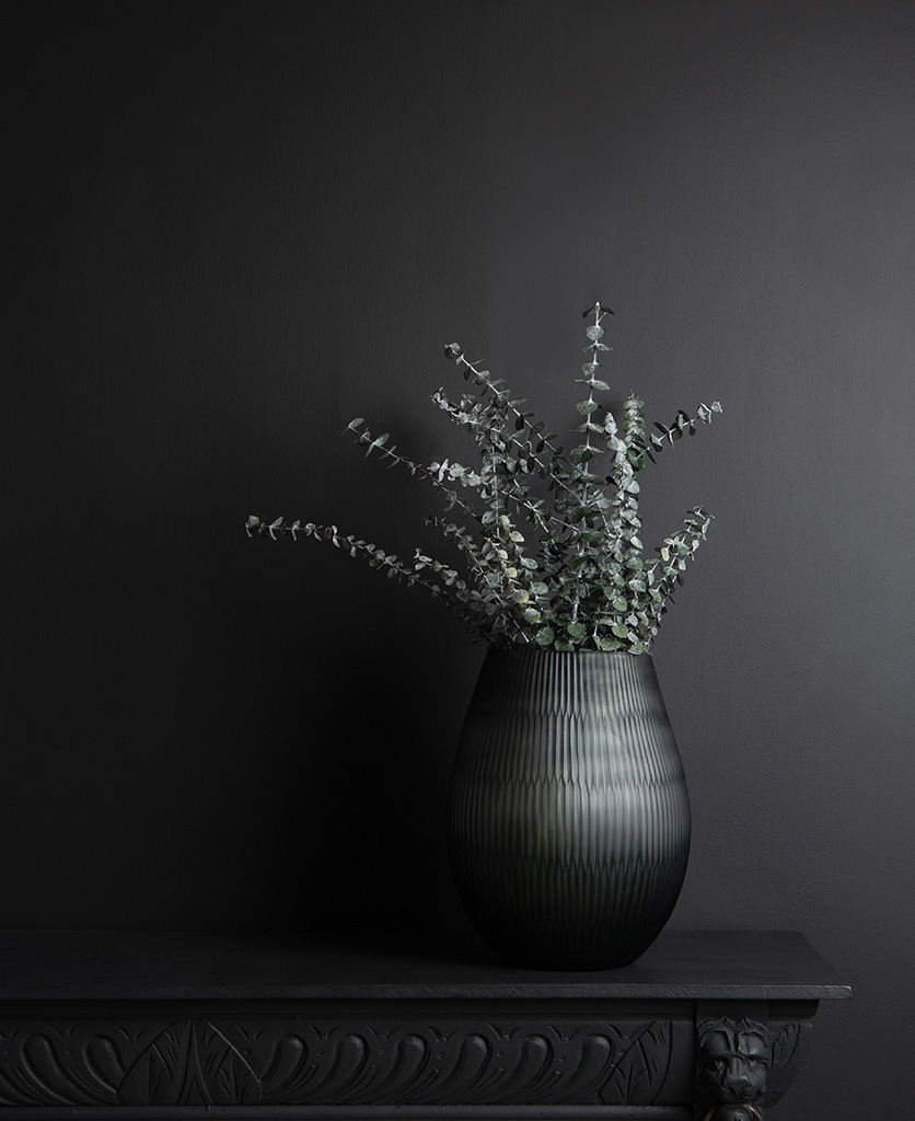 Baby blue eucalyptus with grey textured vase on dark background
