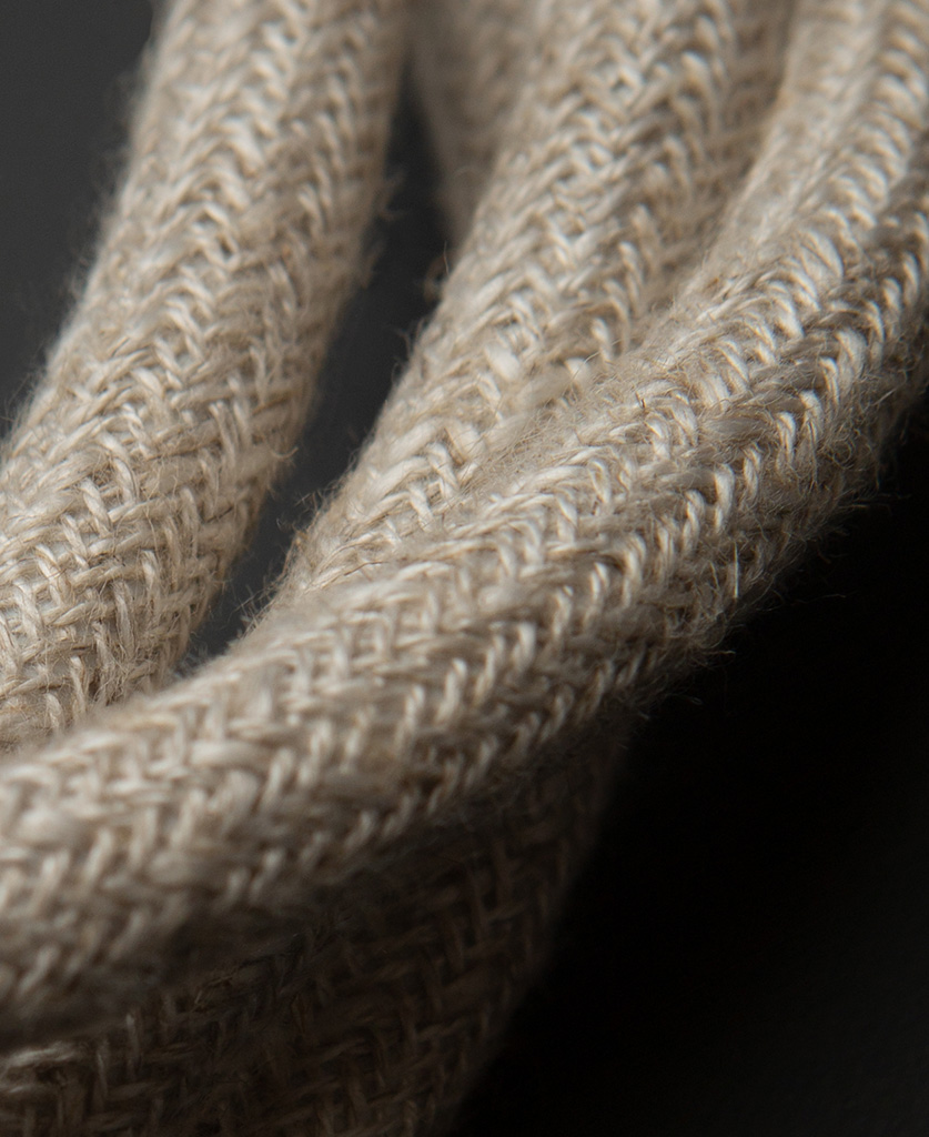 close up of cream course linen fabric extension cable against black background