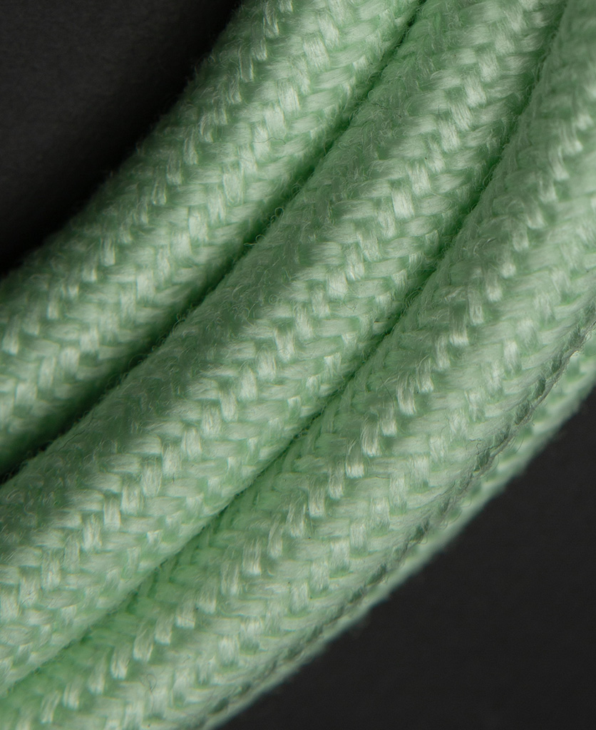 close up of neo mint fabric extension cable against black background