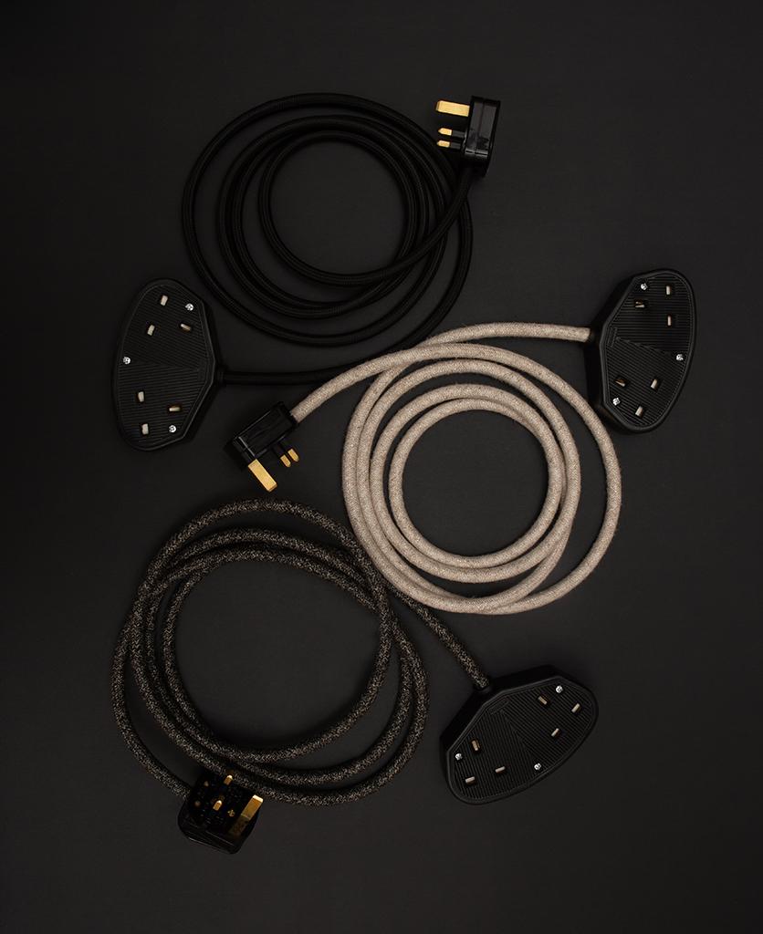linen, black jumper and black extension leads against black background