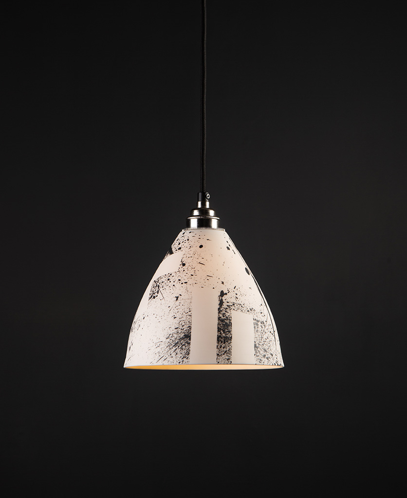 white ceramic pendant light by michael o hare suspended from black fabric cable against black background