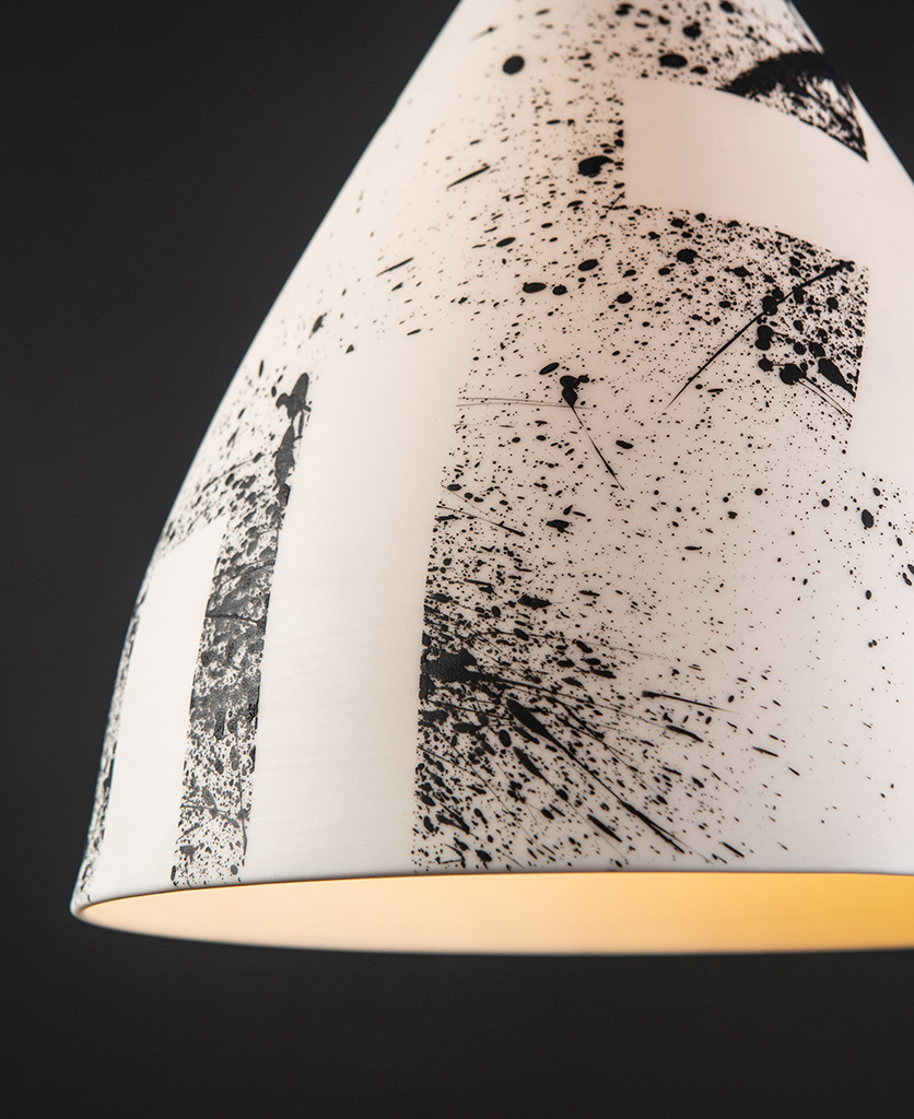 closeup of black paint splatters on whigte porcelain Michael O Hare light shade against black background