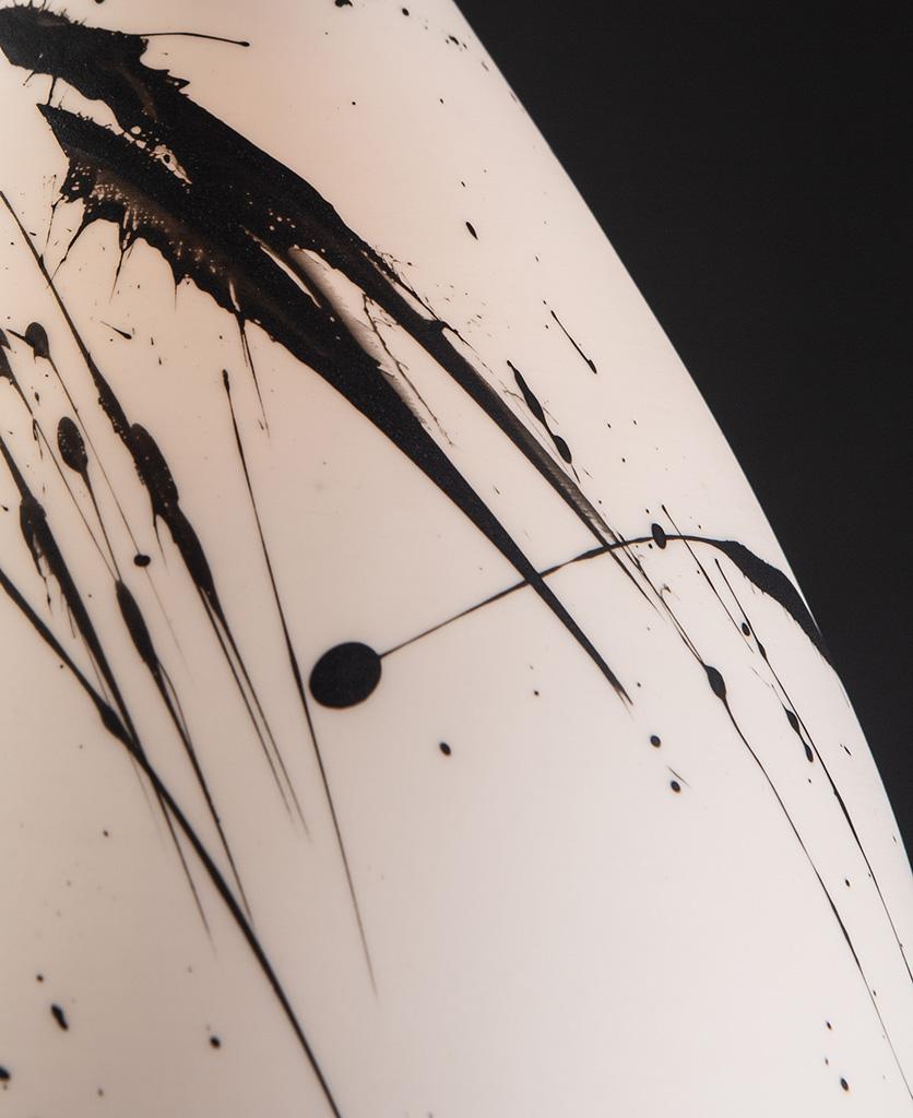 closeup of paint splatters on Michael O hare white porcelain light shade against black background