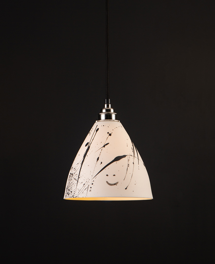 ceramic pendant light in white with black paint splatters on black background
