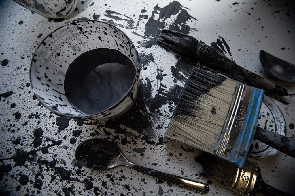 paint brush, spoon and tub of black paint against paint splattered white surface