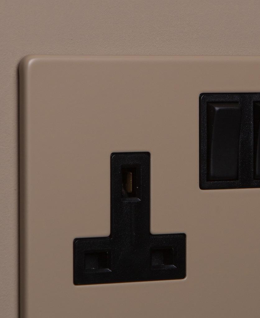 close up of caramel latte double plug socket with black insert on caramel latte background