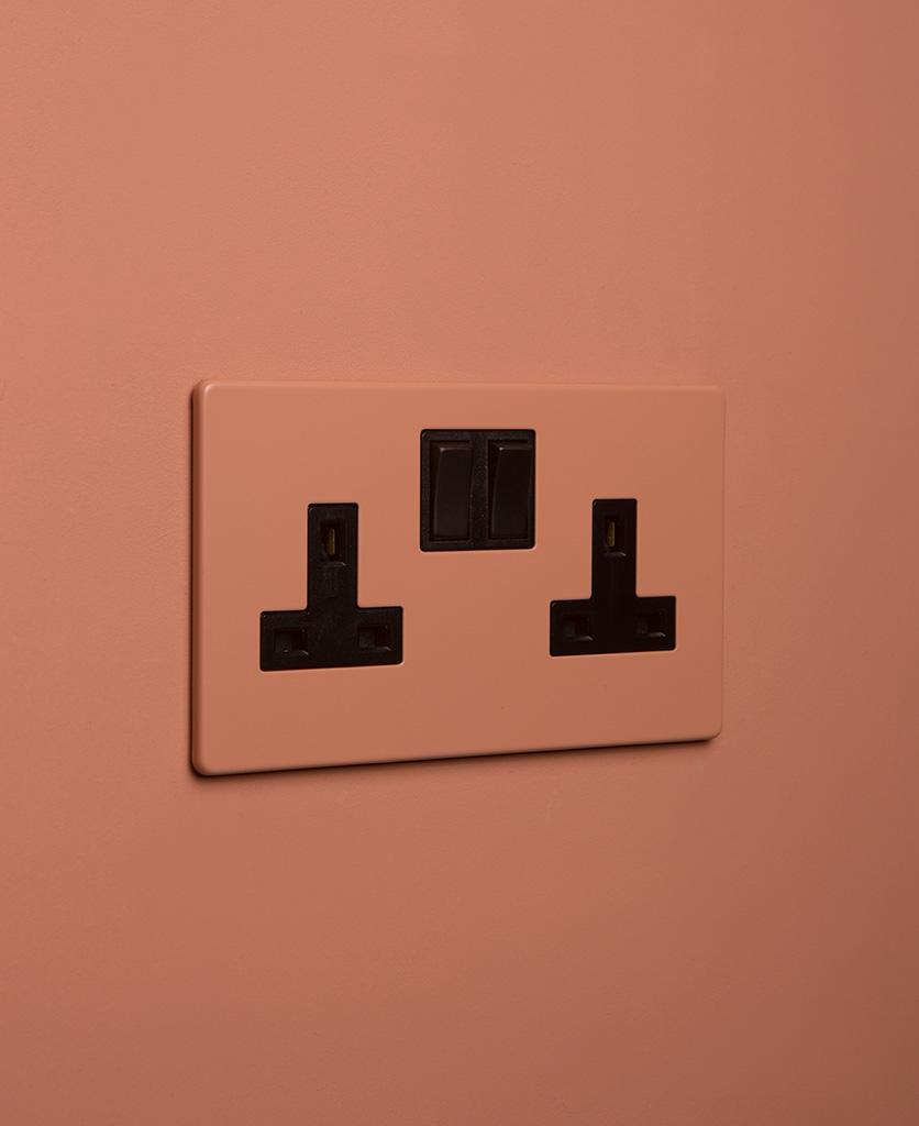 cinnamon double plug socket with black insert on cinnamon background