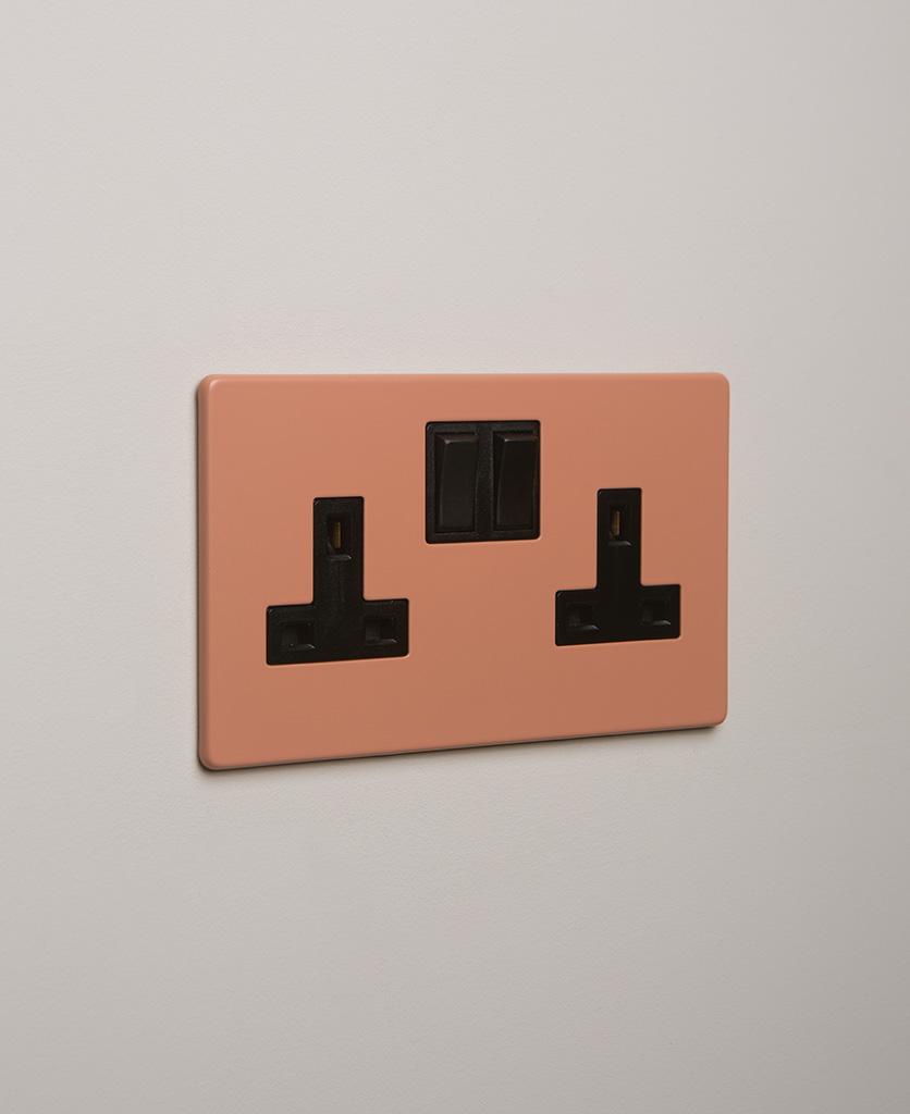 cinnamon double plug socket with black insert on white background