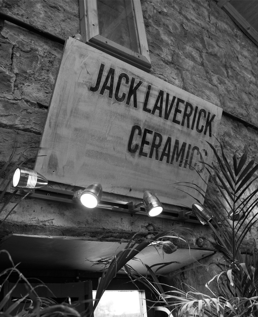 A sign with Jack Lavericks ceramic studio info on against exposed brick wall