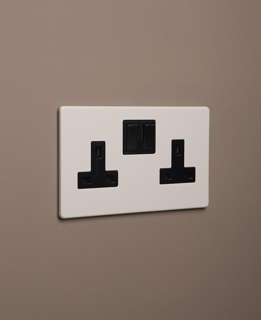 whipped cream double plug socket with black insert on caramel latte background