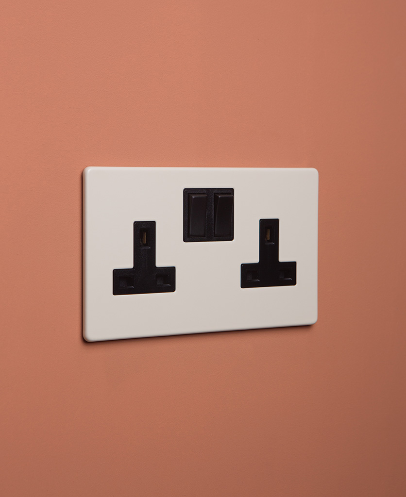 whipped cream double plug socket with black insert on cinnamon background
