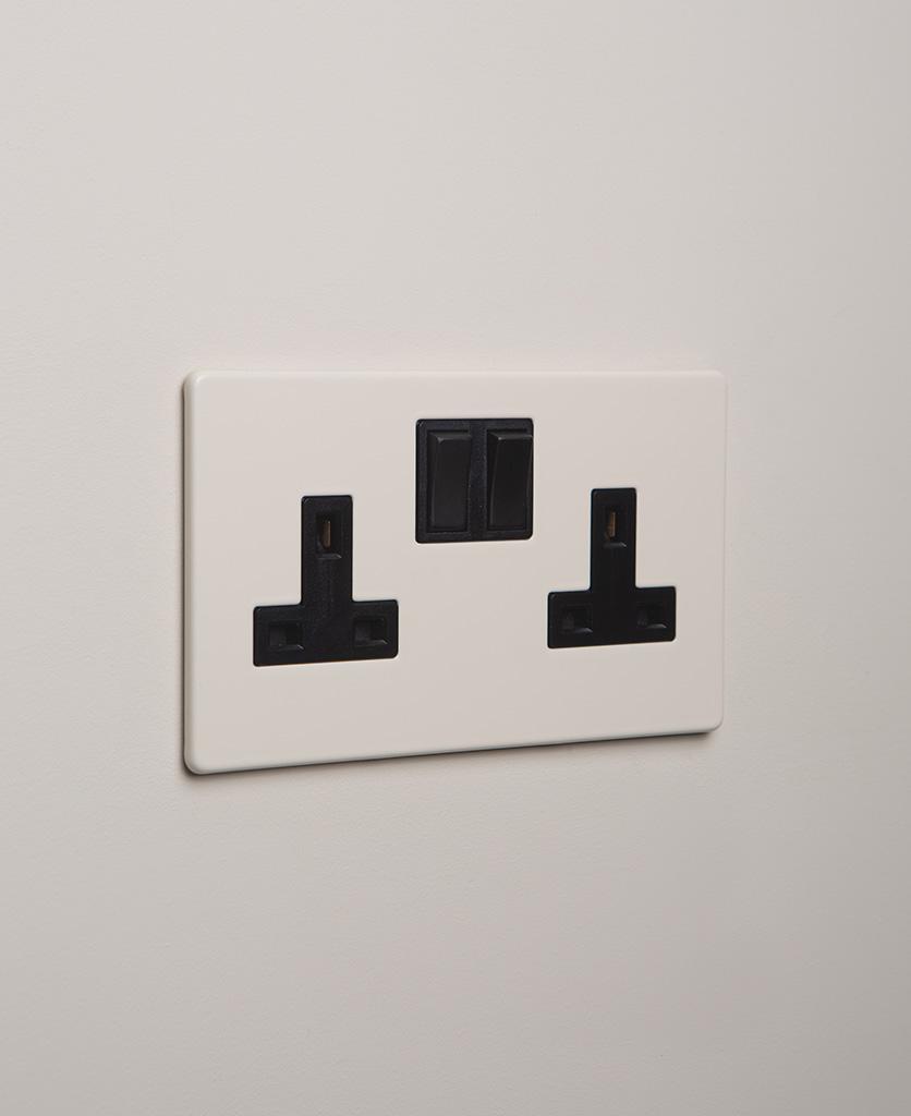 whipped cream double plug socket with black insert on white background
