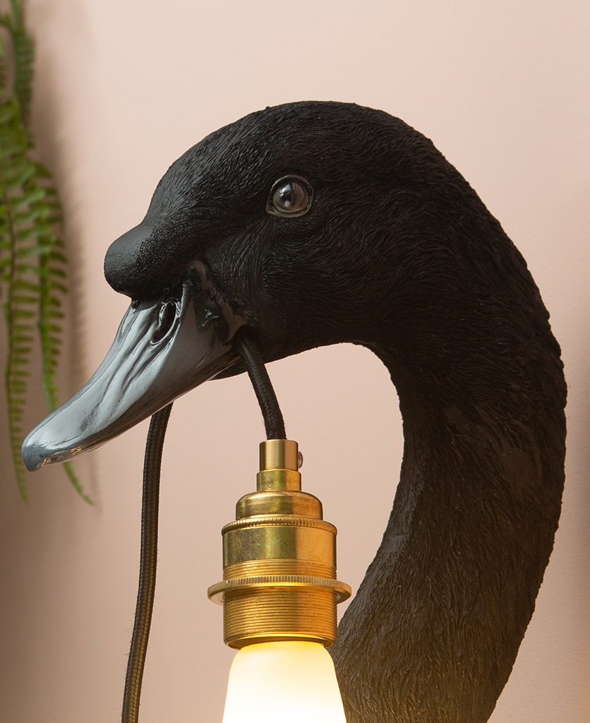 black swan wall light with gold bulb holder and frosted pear bulb close up