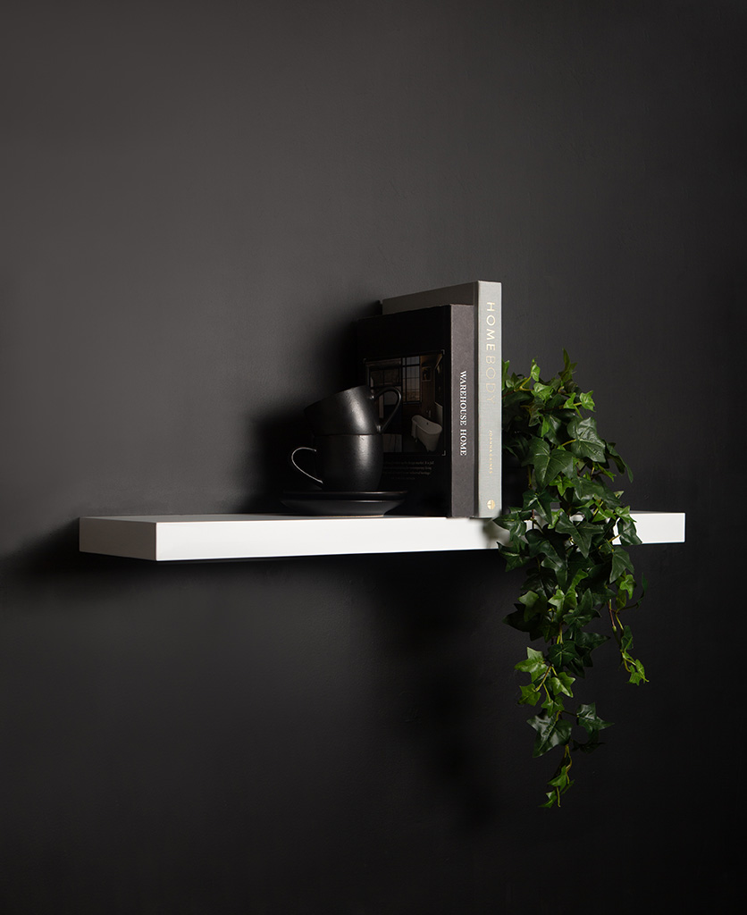 large white floating shelf on black background