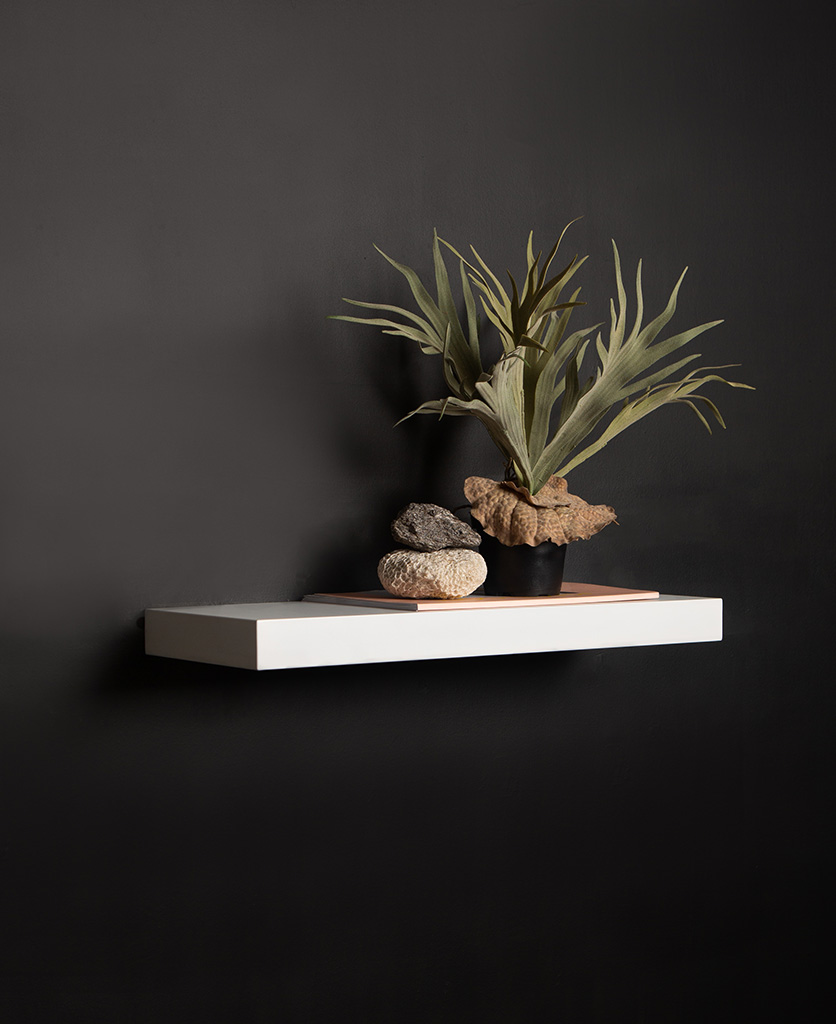 medium white floating shelf on black background