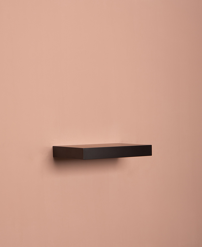 small black floating shelf on pink background