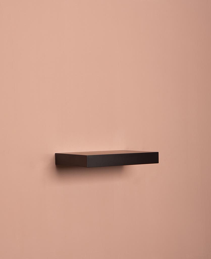small black floating shelf on pink background
