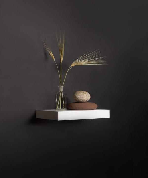 small white floating shelf on black background