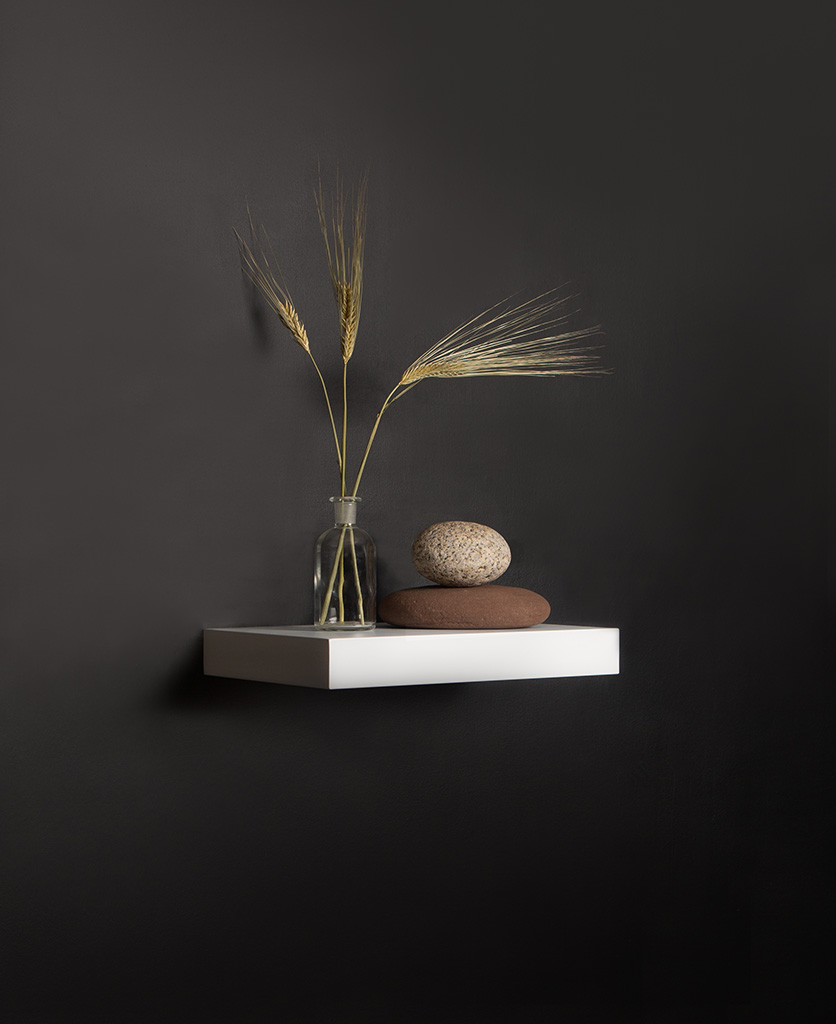 small white floating shelf on black background