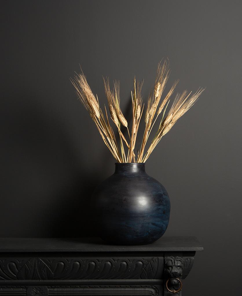 etnik vase with barley bouquet on dark background
