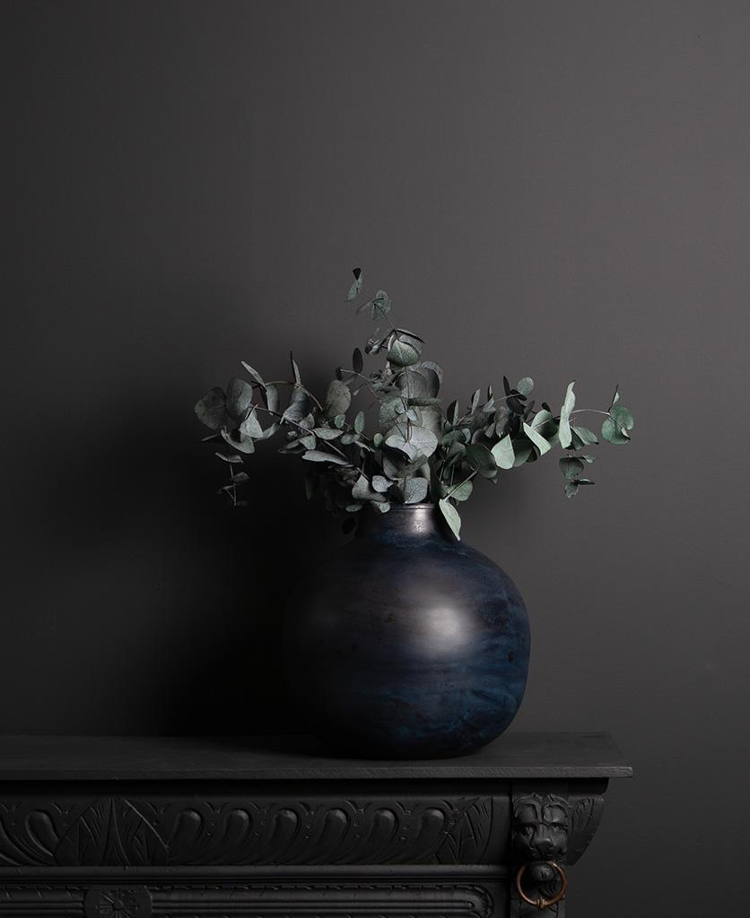etnik vase with eucalyptus cinerea bouquet on dark background